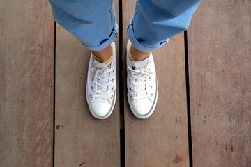 Fashion Female in White Sneaker with Blue Jeans on the Wooden Floor Background Great for Any Use.