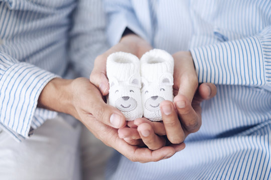 man and pregnant women holding baby shoes