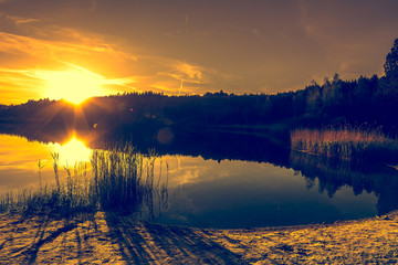 Summer landscape with sunset on the lake. Beautiful orange sundown or sunrise over forest and peaceful water with reflection of sun light, warm scenery in nature.