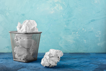 A trash can with papers, one lump is lying next to it. Beautiful unusual background with place for text.