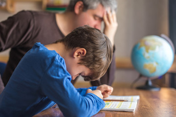 Sad father tired about sons failure on mathematics homework