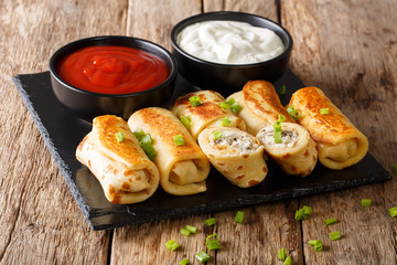 Delicious crepes rolls with chicken, cheese and mushrooms close-up and sauces. horizontal