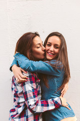 Two Cheerful Women Hugging and Kissing in the Street