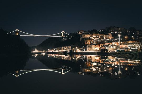 Bristol's Clifton Suspension Bridge reflecting in the river Avon at night.
