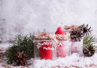 Red candle, twigs and cones on a snow-covered wooden background