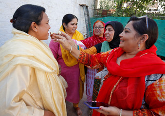 "Activists of ANHAD, a NGO, offer sweets to each other as they celebrate, after Indian government introduced a bill in parliament aimed at prosecuting Muslim men who divorce their wives through the ""triple talaq"", or instant divorce, in Ahmedabad"