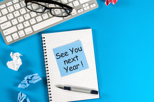 Business message See You Next Year written on notebook, with keyboard, office supplies and empty space at blue table in background
