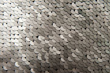 Texture of silver shiny sequins close-up macro abstract background. Fashionable expensive bright fabric with sequins.