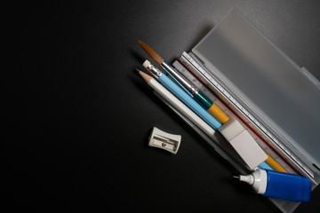 Basic white plastic pencil box with pencil, pen, eraser, sharpener and paintbrush on black background. Close up of pencil box with school supplies on black background.