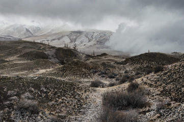 Dramatic winter dark desert steppe on a highland mountain plateau with ranges of  snow peaks on a horizon storm skyline Kurai Altai Mountains Siberia Russia