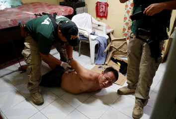 Agents of the Philippine Drugs Enforcement Agency (PDEA) detain a small-time drug trafficking suspect during a raid in Tondo, Manila