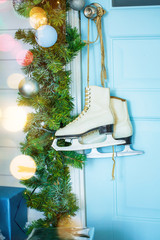 female white leather skates for figure skating hanging on the door handle