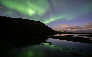 Northern lights background dancing over lake in Abisko national park in Sweden