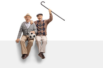 Cheerful seniors with a football seated on a panel