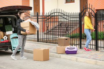 Young couple unloading boxes from their car on moving day