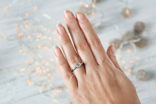 Woman wearing luxury engagement ring on light background, closeup