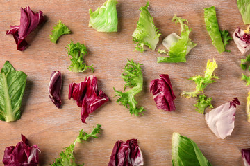 Leaves of different salads on wooden background, top view