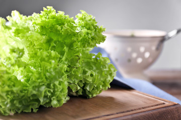 Bunch of fresh green salad on wooden board, closeup