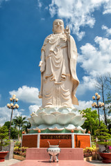 Huge Buddha statue in the garden of the famous Vinh Trang Pagoda at My Tho City, Vietnam