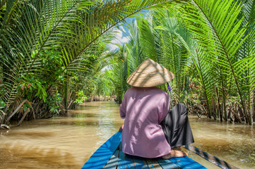 Vietnamese woman paddling a traditional boat in the Mekong delta at Ben Tre island. The Mekong river is a major route for transportation in Southeast Asia.
