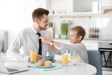Father with son having breakfast in kitchen