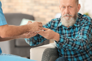 Young caregiver giving cup of tea to senior man at home