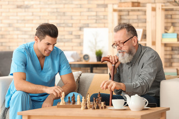 Young caregiver and senior man playing chess at home