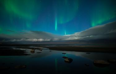 Northern lights dancing over calm lake in Abisko national park in Sweden