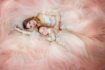 Creative portrait of a beautiful mother and daughter, fashion, in gorgeous long dress