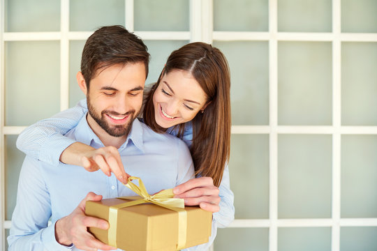 The guy gives a gift box to his girlfriend. Young couple on holiday. St. Valentine's Day.