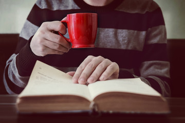 Business man reading book with coffee in coffee shop.