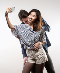 Teenage Girl Taking a Selfie While Being Kissed.