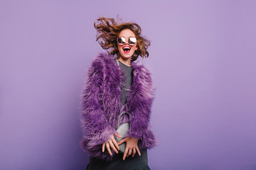 Gorgeous short-haired girl in sunglasses dancing on purple background with happy smile. Laughing female model in elegant fur coat posing in studio with little handbag.