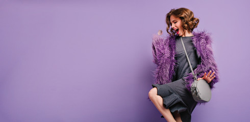 Stunning barefooted woman in trendy fur coat dancing and laughing on photoshoot. Indoor photo of...