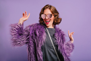 Stunning cute girl with curly brown hair posing with pleasure on purple background. Indoor photo of dancing young lady in trendy fur coat laughing to camera. Fotoväggar