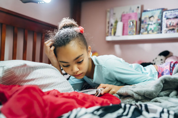 Tween girl reading book in bed