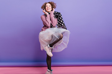 Full-length portrait of gorgeous girl in stylish lush skirt dancing and laughing. Studio shot of fashionable young lady in trendy attire posing on purple background.