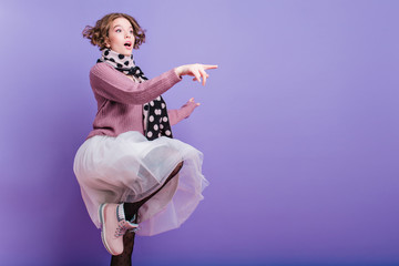 Surprised lady in stylish pink shoes standing on one leg and pointing finger. Indoor photo of cute curly girl in sweater saw something interesting.