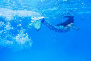 Tween girl in mermaid tail swimming in pool