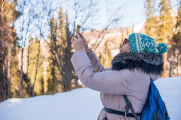 Woman 50 years old taking photo in the mountains in winter, Almaty, Kazakhstan