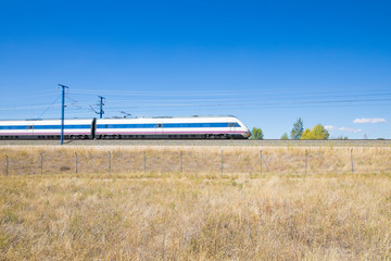 locomotive of fast speed train on railway in a landscape with blue sky in countryside of Spain, Europe
