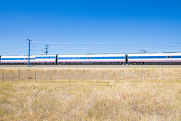 wagons of high speed train on railway in a landscape with blue sky in countryside of Spain, Europe