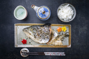 Traditional barbecue Japanese Kama Yaki salmon fish head with rice as to view on a plate