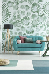 Blue sofa against leaves wallpaper