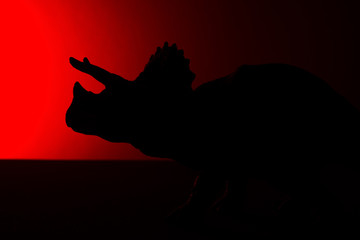 triceratops shadow with red light in dark