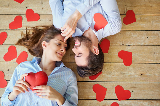 Couple lying on the wooden floor with hearts view from above. Valentine's Day.