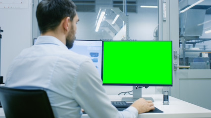 Engineer/ Technician Working on a Personal Computer with Two Displays, One Has a Green Screen Chroma Key Template Great for Mockup. Out of the Office Window Components Manufacturing Factory is Seen.