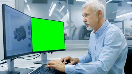 Engineer Working on a Computer with Two Displays, One has Chroma Key Great for Mockup Template and other Component in CAD Program. Out of the Office Window Components Manufacturing Factory is Visible.