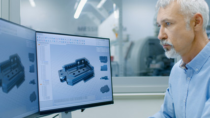 Engineer Working on a Personal Computer with Two Displays, He's Designing New Essential Component in CAD Program. Out of the Office Window Components Manufacturing Factory is Visible.