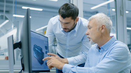 Industrial Designer Has Product Discussion with Senior Engineer While Working in CAD Program, Designing New Component. He Works on Personal Computer with Two Monitors.